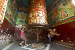 Unidentified children have fun with spinning Big Tibetan Buddhist prayer wheel at Boudhanath Stupa. Stock Image