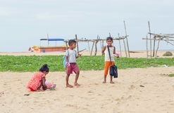 Unidentified children playing together on sand beach near small village. NEGOMBO, SRI LANKA - DEC 21, 2017: Unidentified children playing together on sand beach Royalty Free Stock Photos