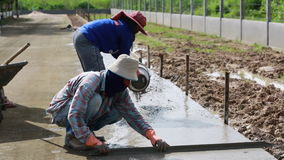 Unidentified Construction workers make shape concrete road. Road work, street repair stock footage