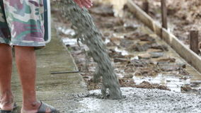 Unidentified Construction workers pour concrete mix. From cement mixer stock video
