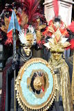 An unidentified couple of man and woman dress elaborate fancy dresses with gold masks, red and black feather hats during Venice Ca. VENICE, ITALY – FEBRUARY 8 Stock Photography