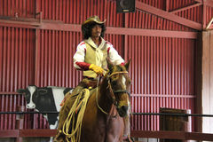 The unidentified cowboy is showing tourists how to ride a horse. Royalty Free Stock Photography