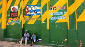 Unidentified Cuban male and female sitting underneath colorful revolution Mural in Havana, Cuba. Stock Image