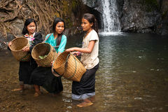 Unidentified cute Asian girls near tropical waterfall. Laos Royalty Free Stock Photos
