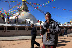 An unidentified devotee offer prays at the Buddhist pilgrimage center Boudhanath Stupa Stock Photos