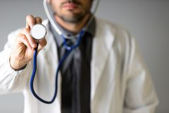 An unidentified doctor grabs a stethoscope to the camera to check the patient royalty free stock images