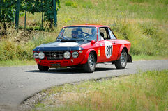 Unidentified drivers on a black and red vintage Lancia Fulvia racing car Stock Photos