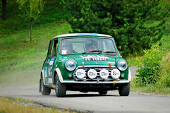 Unidentified drivers on a green vintage Mini Innocenti racing car Royalty Free Stock Photo