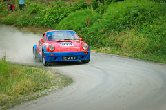 Unidentified drivers on a red and blue vintage Porsche 911 S racing car Stock Photo