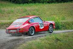 Unidentified drivers on a red vintage Porsche 911 S racing car Royalty Free Stock Photos