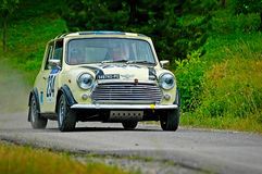 Unidentified drivers on a yellow vintage Mini Cooper racing car Stock Photo