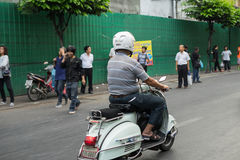 Unidentified driving a Vespa motorcycle. BANGKOK, THAILAND - February 2, 2017: Unidentified driving a Vespa motorcycle, scooter, people walking on the side Royalty Free Stock Photography