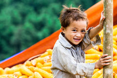 Unidentified ethnic child playing on a bundle of corns Royalty Free Stock Photo
