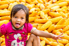 Unidentified ethnic child playing on a bundle of corns Stock Image