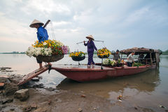 Unidentified farmers carry flowers to the market Stock Images