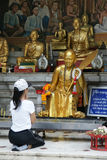 Unidentified female tourism pray to monk statue at Thailand Royalty Free Stock Photo