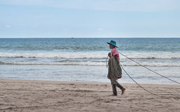 Unidentified fishermаn carries rope for net royalty free stock photography