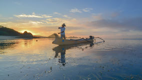 Unidentified fisherman ready to work in the boat early morning during sunrise moment Royalty Free Stock Image