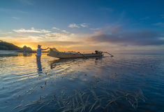 Unidentified fisherman ready to work in the boat early morning during sunrise moment Stock Image