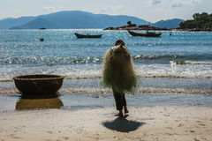 Unidentified fishermen is working on the beach in Nha Trang, Vie Royalty Free Stock Photo