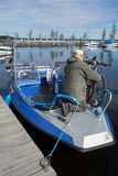 Unidentified fishing guide ties touring bikes to a fishing boat in marina by the lake Saimaa, Finland stock images