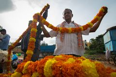 An unidentified flower seller buys marigold garlands from a wholesaler at Local market in Hospet ,Karnataka South India. stock image