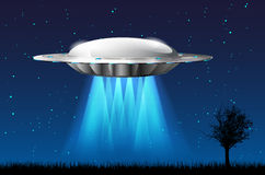 Unidentified flying object with rays and starry night sky Royalty Free Stock Image