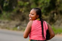 Unidentified Ghanaian beautiful woman in pink shirt with braids. CENTRAL REGION, GHANA - Jan 17, 2017: Unidentified Ghanaian beautiful woman in pink shirt with royalty free stock image