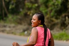 Unidentified Ghanaian beautiful woman in pink shirt with braids. CENTRAL REGION, GHANA - Jan 17, 2017: Unidentified Ghanaian beautiful woman in pink shirt with stock photography