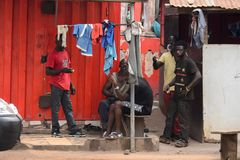 Unidentified Ghanaian group of people gather near the shack on. KUMASI, GHANA - Jan 16, 2017: Unidentified Ghanaian group of people gather near the shack on the stock image