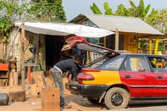 Unidentified Ghanaian man bends down to opened trunk in local v. CENTRAL REGION, GHANA - Jan 17, 2017: Unidentified Ghanaian man bends down to opened trunk in stock photos