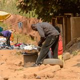 Unidentified Ghanaian man bends down to pick up food in local v. CENTRAL REGION, GHANA - Jan 17, 2017: Unidentified Ghanaian man bends down to pick up food in stock photo