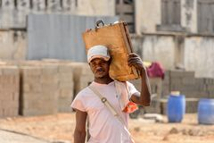 Unidentified Ghanaian man carries an old case on his shoulder i. CENTRAL REGION, GHANA - Jan 17, 2017: Unidentified Ghanaian man carries an old case on his royalty free stock photography