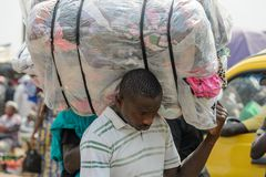 Unidentified Ghanaian man carries a plastic bag on his shoulder stock photos