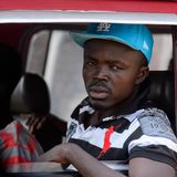 Unidentified Ghanaian man looks out of the red car's window in. CENTRAL REGION, GHANA - Jan 17, 2017: Unidentified Ghanaian man looks out of the red car's window royalty free stock images