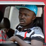 Unidentified Ghanaian man looks out of the red car's window in. CENTRAL REGION, GHANA - Jan 17, 2017: Unidentified Ghanaian man looks out of the red car's window stock photo