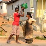 Unidentified Ghanaian man puts a basket on woman's head in loca. CENTRAL REGION, GHANA - Jan 17, 2017: Unidentified Ghanaian man puts a basket on woman's head in stock images