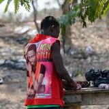Unidentified Ghanaian man in red colored shirt cuts an onion fr. BRONG AHAFO, GHANA - JAN 15, 2017: Unidentified Ghanaian man in red colored shirt cuts an onion royalty free stock image