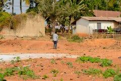 Unidentified Ghanaian man walks from behind in local village. P. CENTRAL REGION, GHANA - Jan 17, 2017: Unidentified Ghanaian man walks from behind in local royalty free stock photo