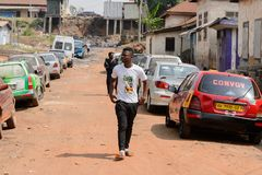 Unidentified Ghanaian man in white shirt walks along the road i. CENTRAL REGION, GHANA - Jan 17, 2017: Unidentified Ghanaian man in white shirt walks along the stock photo