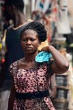 Unidentified Ghanaian woman in beautiful dress with braids carr. KUMASI, GHANA - Jan 16, 2017: Unidentified Ghanaian woman in beautiful dress with braids carries stock image