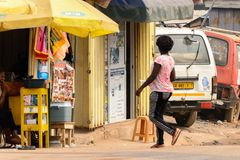 Unidentified Ghanaian woman with braids from behind walks to th. KUMASI, GHANA - Jan 16, 2017: Unidentified Ghanaian woman with braids from behind walks to the stock images