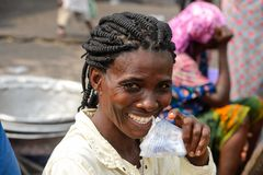 Unidentified Ghanaian woman with braids smiles in Elmina port. ELMINA, GHANA -JAN 18, 2017: Unidentified Ghanaian woman with braids smiles in Elmina port royalty free stock photography