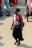 Unidentified Ghanaian woman with braids walks at the Kumasi mar. KUMASI, GHANA - JAN 15, 2017: Unidentified Ghanaian woman with braids walks at the Kumasi market royalty free stock photo