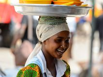 Unidentified Ghanaian woman carries a tray on her head at the K royalty free stock image