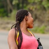 Unidentified Ghanaian woman in pink shirt with braids smiles in. CENTRAL REGION, GHANA - Jan 17, 2017: Unidentified Ghanaian woman in pink shirt with braids stock photos