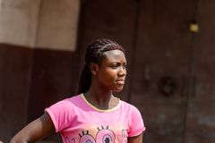 Unidentified Ghanaian woman in pink shirt with braids stands in. CENTRAL REGION, GHANA - Jan 17, 2017: Unidentified Ghanaian woman in pink shirt with braids royalty free stock photography