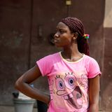 Unidentified Ghanaian woman in pink shirt with braids stands in. CENTRAL REGION, GHANA - Jan 17, 2017: Unidentified Ghanaian woman in pink shirt with braids stock photos