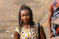Unidentified Ghanaian woman wears colored dress and braids on h. ACCRA, GHANA - JAN 8, 2017: Unidentified Ghanaian woman wears colored dress and braids on her royalty free stock photos
