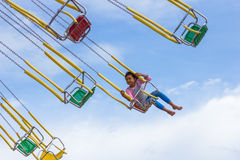 Unidentified girl on the chain swing carousel Royalty Free Stock Images